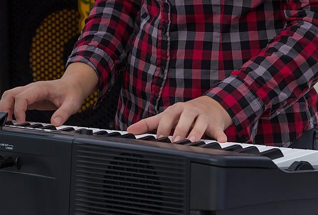 man in checkered shirt playing a digital piano