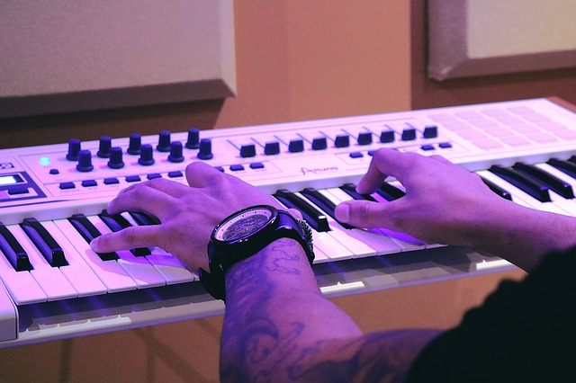Man with a tattooed hand playing a digital piano